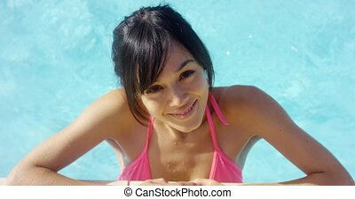 Smiling brunette in pink bikini stands in pool on beautiful...