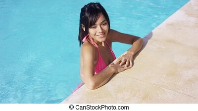 Sexy young woman standing in a swimming pool resting her...