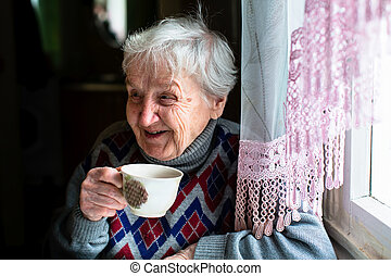 Happy elderly woman portrait sitting at the table and drink...