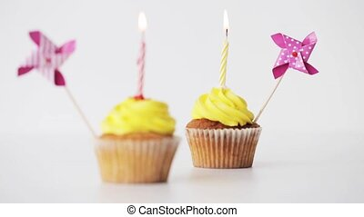 birthday cupcakes with burning candle and pinwheel -...