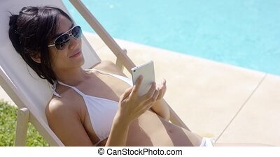 Woman in white bikini checks her cell phone while relaxing...