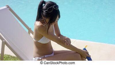 Young woman applying sunscreen as she sits sunbathing on a...