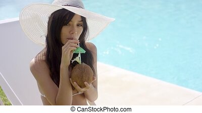 Smiling young woman sipping a coconut cocktail - Smiling...
