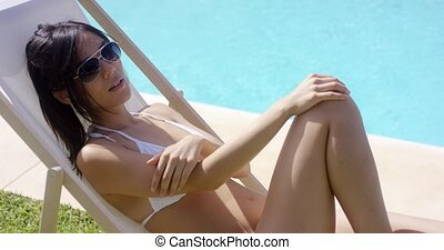 Woman in white bikini wearing sunglasses as she relaxes by...