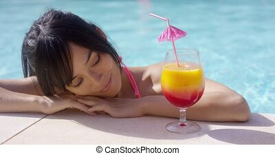 Happy young woman eyeing a large tropical cocktail as she...