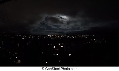 Full moon behind clouds at night in the city