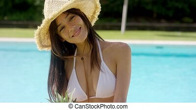 Laughing woman in white bikini and straw hat stands by pool...