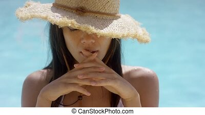 Exotic brunette wearing straw hat while in pool holds hands...