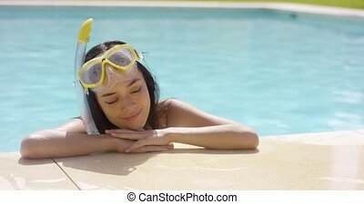 Woman in snorkel and goggles rests by pool and smiles to...