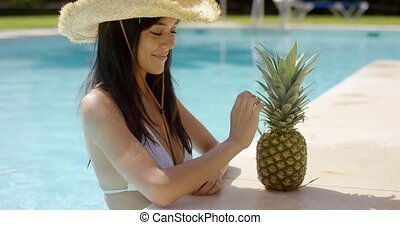 Young woman sipping a pineapple cocktail - Young woman in a...