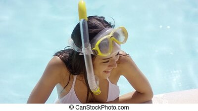 Smiling woman in swim suit wears goggles and snorkel while...