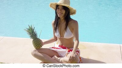 Woman with pineapple and straw hat sits by pool with her...