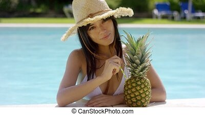 Sunbathing beauty drinks from a pineapple while standing in...