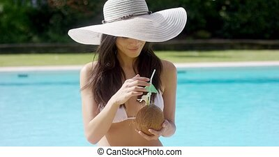 Beautiful woman sipping a coconut cocktail - Beautiful woman...
