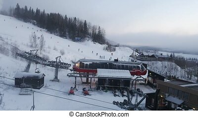 A view from cable car cabin on ski resort and ski path with skiing people. Sweden