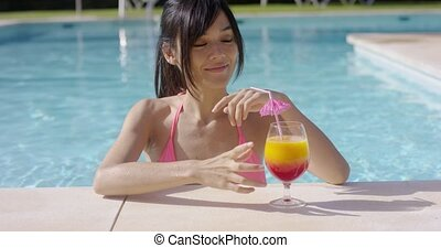 Pretty young woman sipping a cocktail in a pool