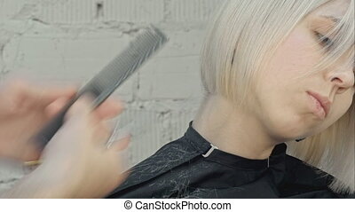 Hairdresser cuts blond hair with scissors. Professional shot...