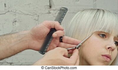 Young beautiful woman having her hair cut at the...