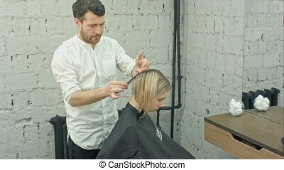 Happy young woman and hairdresser making hair styling at salon