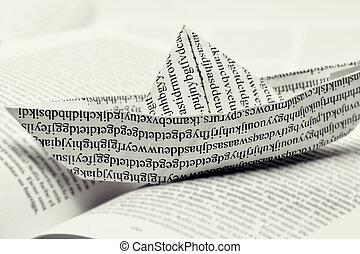 paper boat on an open book - closeup of a paper boat, made...