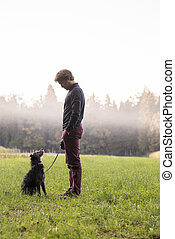 Man in front of foggy woods with dog