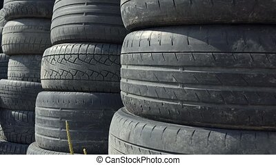 Stacks of old used car tyres 4K zoom in shot. Disposal site