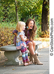 Happy mother and daughter having fun time at the park. -...