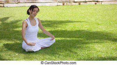 Young woman meditating in nature sitting cross-legged on...