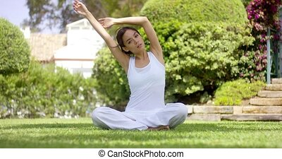 Gorgeous young woman in white sitting on lawn - Gorgeous...