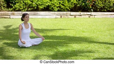 Lovely young woman meditating in the garden in summer...