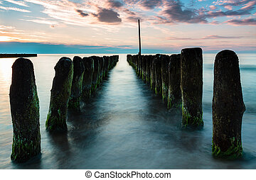 Wooden poles breaking sea water, long exposure. Poland,...