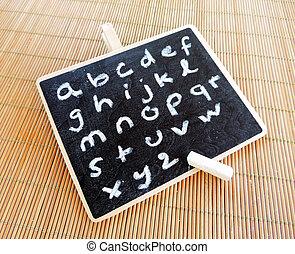 Alphabetical letters written with chalk on a blackboard.