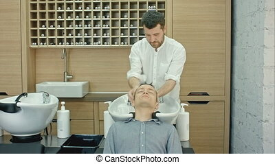 Barber washing client's hair in barbershop. Professional...