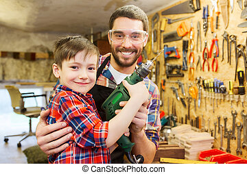 father and son with drill working at workshop - family,...