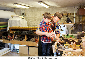 father and son with chisel working at workshop - family,...