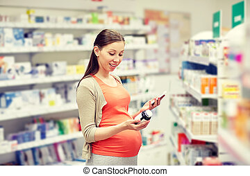 happy pregnant woman with smartphone at pharmacy