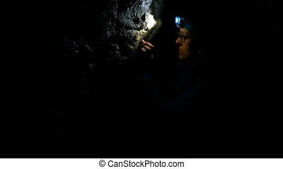 Woman Looking Around in the Cave - Adult caucasian woman...