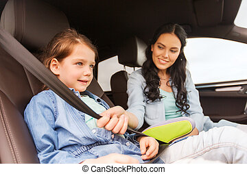 happy woman fastening child with seat belt in car - family,...