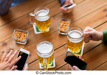 close up of hands with smartphones and beer at bar - people,...