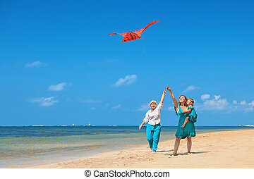 Grandmother, mother, and child launching kite on ocean beach