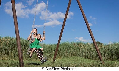 Beautiful young woman with a charming little girl swinging outdoors