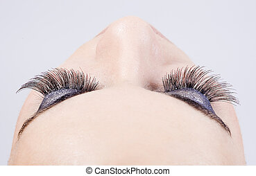 young girl make up - detail of the make up of eyelashes in a...