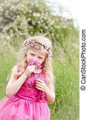 child smelling pink rose