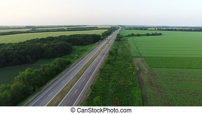 Cars driving along a country road in the woods on a summer day. Aerial shot