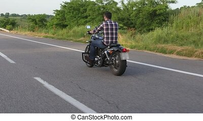 Man on a motorcycle rides on the road. Overhead shot