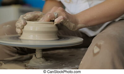 Hands working on pottery wheel - Close up shot of craftsman...