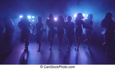 Shilouettes of female dancers group sensually walking on a...