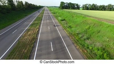 Cars driving on the road past the field. Overhead shot -...