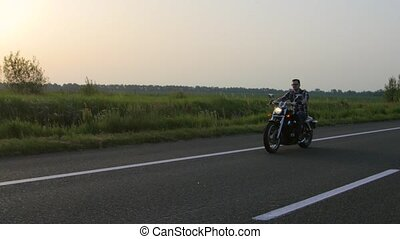 Man on a motorcycle rides, sunset. Overhead shot - Man on a...