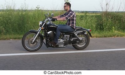 Man in glasses rides a motorcycle and is looking forward....